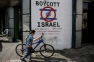 A Palestinian boy walks with his bicycle past past a mural calling people to boycott Israeli goods in the al-Azzeh refugee camp near the West Bank city of Bethlehem on September 17, 2014. There have been growing calls for an economic, academic and cultural boycott of Israel over alleged human rights violations, including in Gaza, where a recent 49-day conflict has killed more than 2,100 Palestinians, most of them civilians. AFP PHOTO/ AHMAD GHARABLI / AFP PHOTO / AHMAD GHARABLI