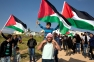 Arab Israelis march with Palestinian flages during a rally commemorating Land Day on March 30, 2016 in the Umm Al-Hiran village, which is not recognized by the Israeli government, near the southern city of Beersheba in the Negev desert. On the annual Land Day, demonstrations are held to remember six Arab Israeli protesters who were shot dead by Israeli police and troops during mass protests in 1976 against plans to confiscate Arab land in the Galilee. / AFP PHOTO / MENAHEM KAHANA