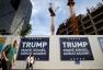 People walk past signs bearing the name of U.S. President-elect Republican Donald Trump in Tel Aviv, Israel November 14, 2016. REUTERS/Baz Ratner
